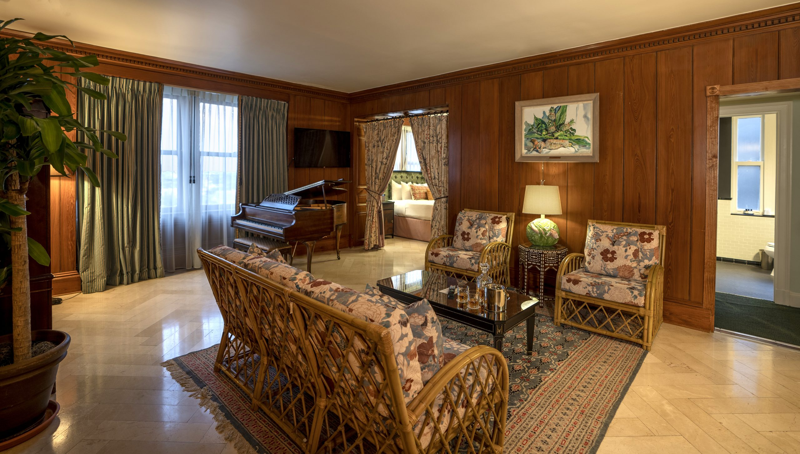 Hotel suite in New Orleans with a baby grand piano in the seating area with sofa and two chairs