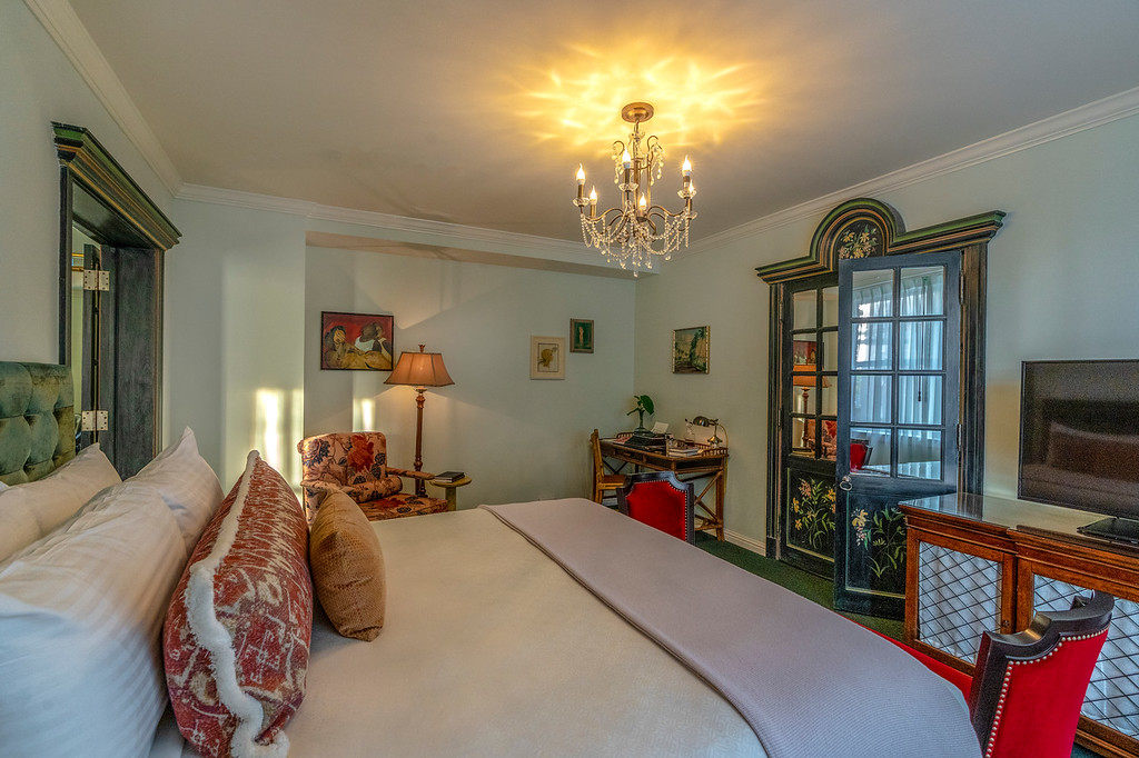 King bed with a red chair& ornate doors leading to the seating area at our Uptown New Orleans hotel.
